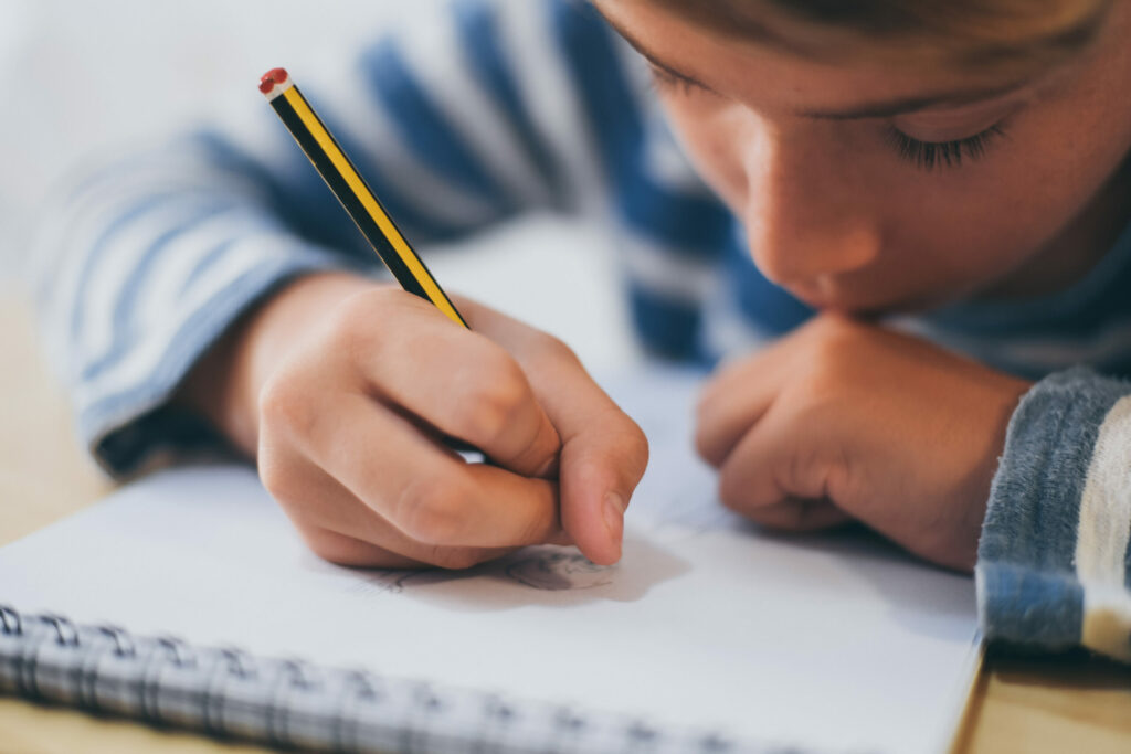 Close up of boy writing on paper